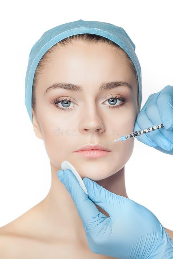 Atrakcyjna kobieta przy chirurgią plastyczną z strzykawką w jej twarzy fotografia stock