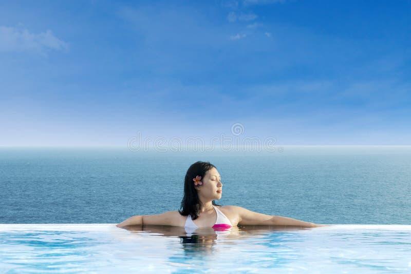 Atrakcyjna kobieta relaksuje przy nieskończoność pływackim basenem zdjęcia stock