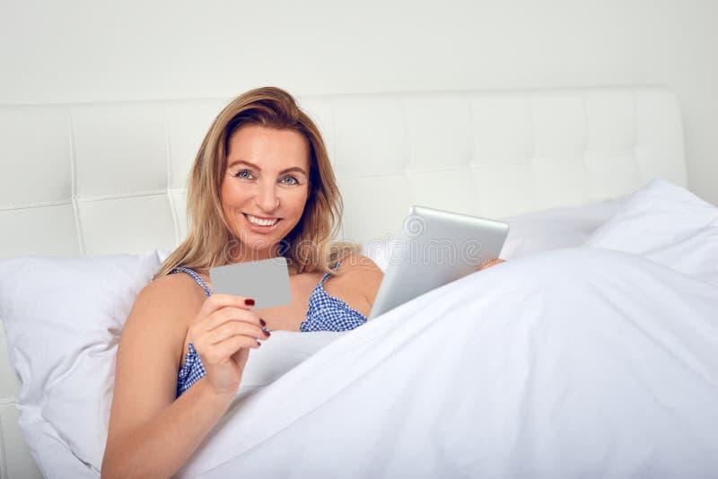 Atrakcyjna kobieta relaksuje w łóżku robi online zakupy obraz royalty free