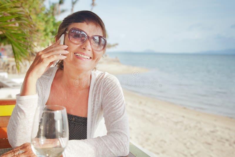 Atrakcyjna kobieta 50 rok z telefonem komórkowym zdjęcie royalty free