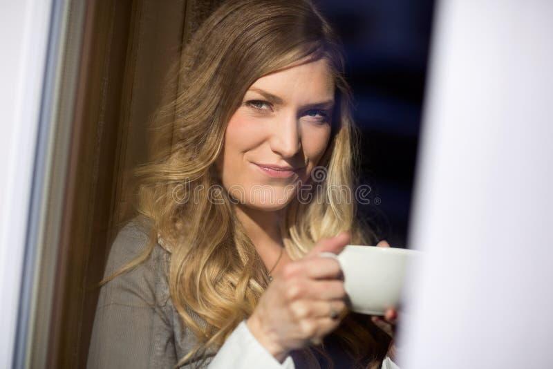 Atrakcyjna kobieta Trzyma filiżankę Przy kawiarnią zdjęcia stock