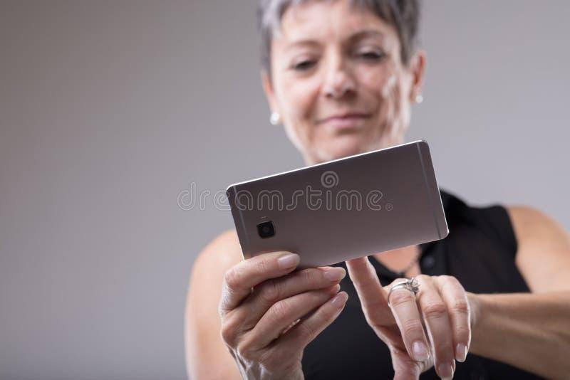 Atrakcyjna kobieta używa telefon komórkowego zdjęcia stock