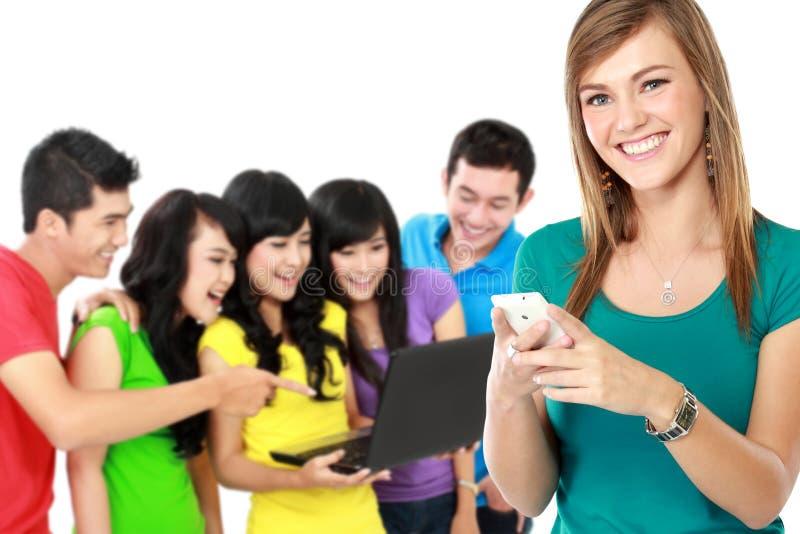 Atrakcyjna kobieta używa telefon komórkowego przy plecy podczas gdy jej przyjaciel zdjęcie royalty free
