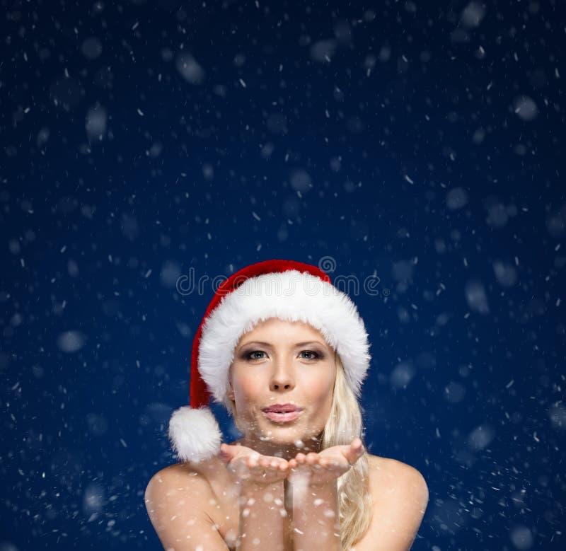 Atrakcyjna kobieta w Bożych Narodzeń nakrętki ciosów buziaku fotografia royalty free