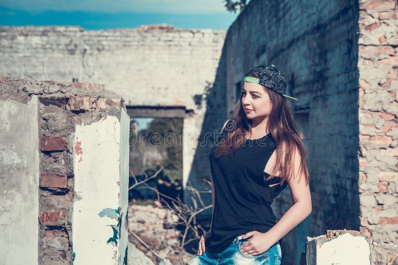 Atrakcyjna kobieta w cajgu i filiżanki stroju pozuje w starym rujnującym fabryka domu obraz royalty free