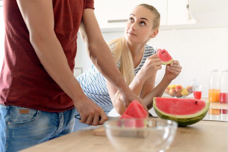 atrakcyjna kobieta w kuchennego łasowania czerwonym arbuzie i patrzeć jej męża, para w ich wielkiej współczesnej białej kuchni obrazy royalty free