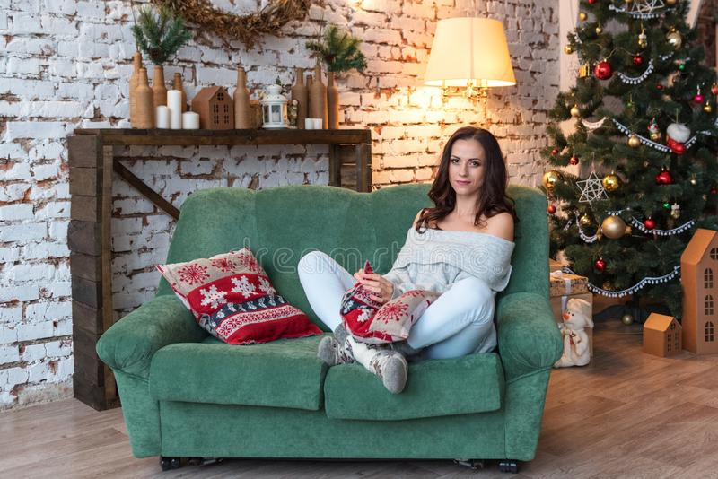 Atrakcyjna kobieta w rocznika puloweru przytulenia ochraniaczach siedzi na wygodnej kanapie w choinka dekorującym żywym pokoju zdjęcia royalty free