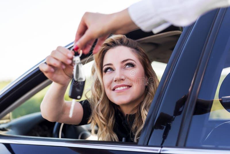 Atrakcyjna kobieta w samochodzie dostaje samochodowych klucze Czynsz lub zakup samochód obraz royalty free