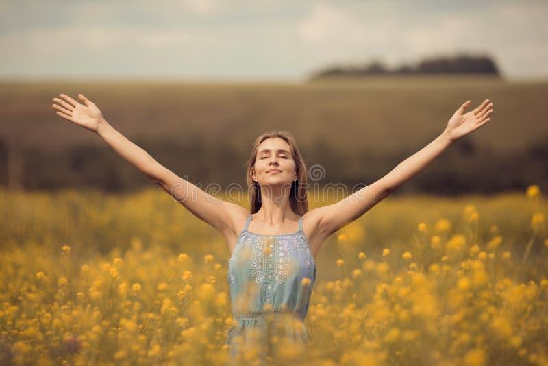 atrakcyjna kobieta w sukni przy kwiatu polem obraz stock