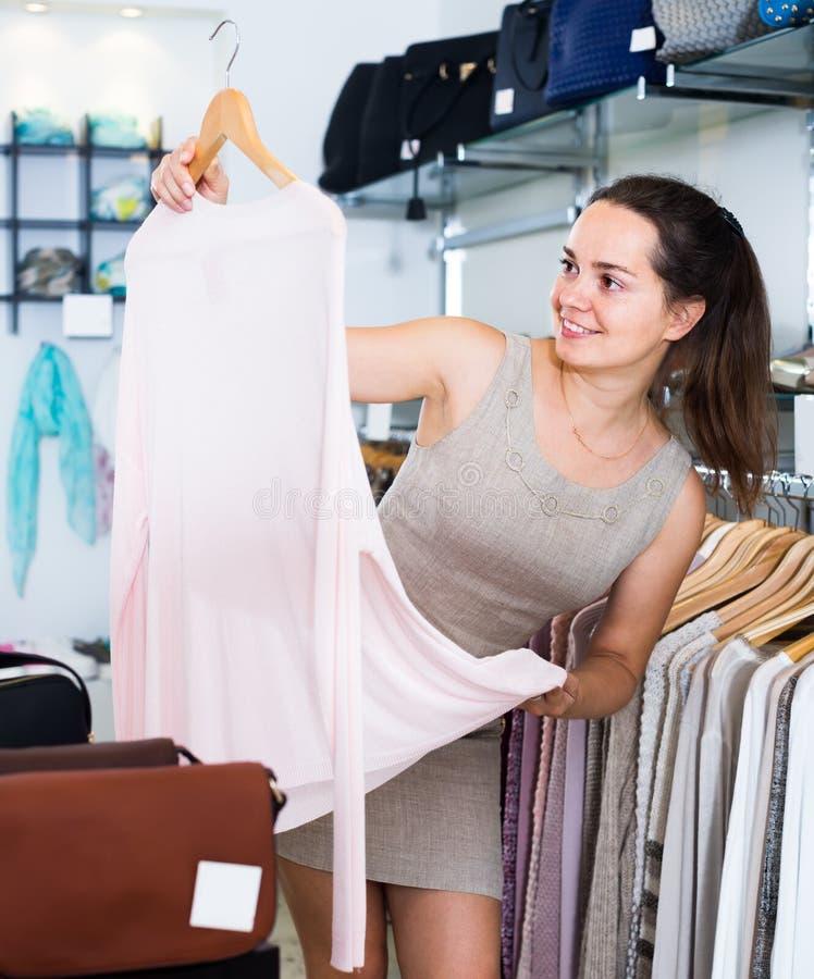Atrakcyjna kobieta wybiera nową bluzkę w odzież sklepie zdjęcie stock