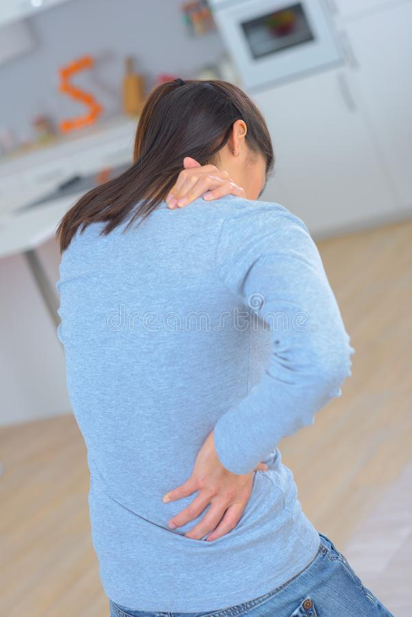 Atrakcyjna kobieta z bólem pleców w domu fotografia royalty free