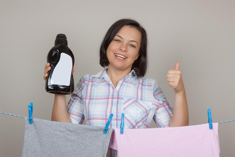 Atrakcyjna kobieta z Czarnym Plastikowym Detergentowym butelki obwieszeniem Mokrym zdjęcia royalty free