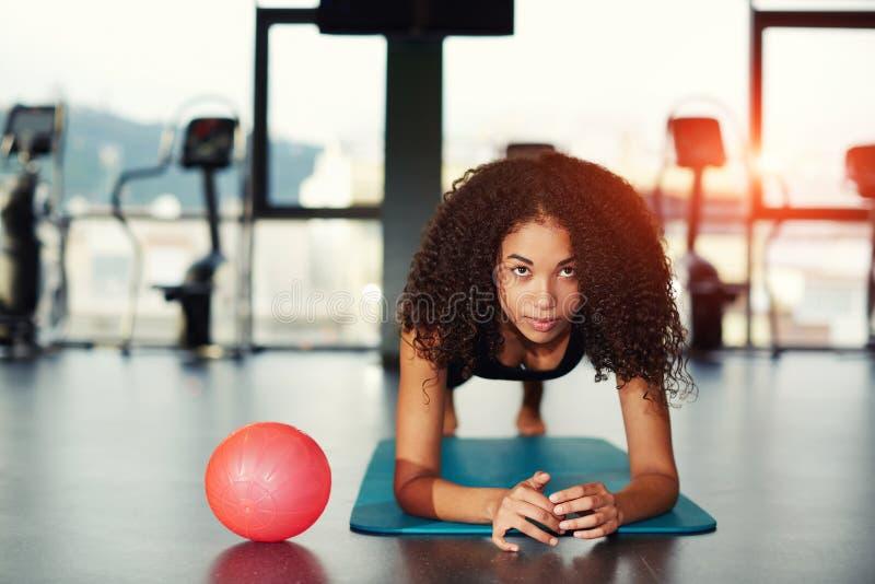 Atrakcyjna kobieta z kędzierzawym włosy opiera na jej łokciach pracujących przy gym out zdjęcia royalty free