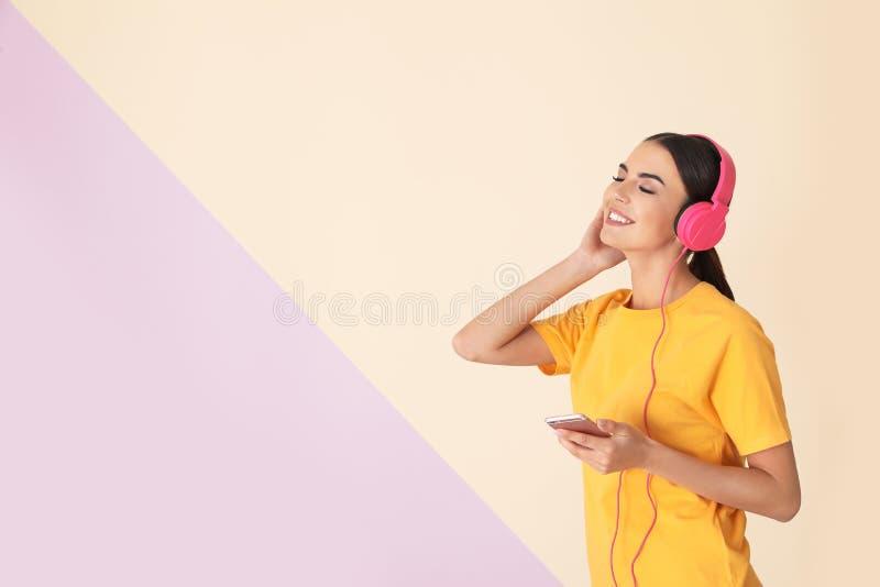 Atrakcyjna kobieta z telefonem komórkowym cieszy się muzykę w hełmofonach na koloru tle zdjęcie royalty free