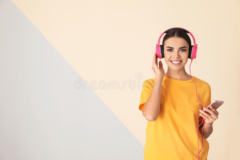 Atrakcyjna kobieta z telefonem komórkowym cieszy się muzykę w hełmofonach na koloru tle obrazy royalty free