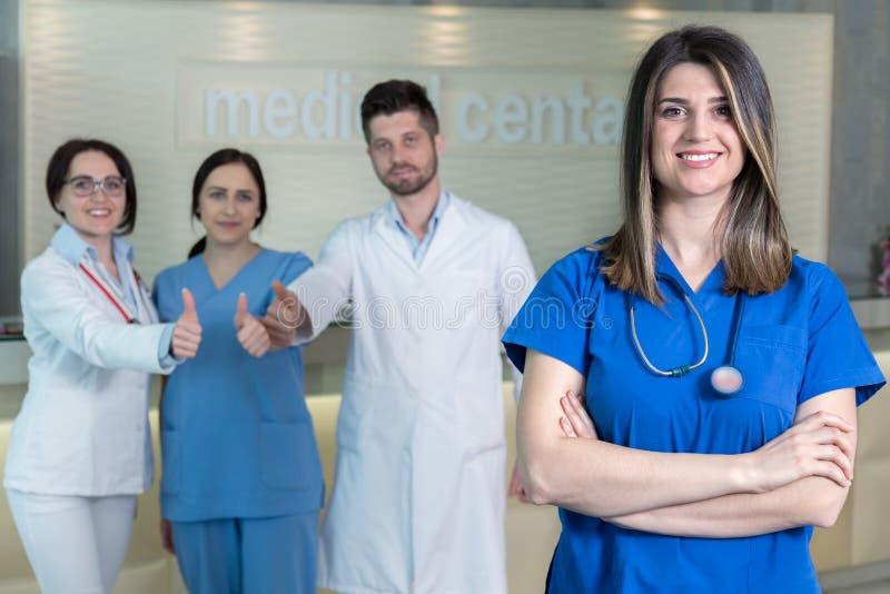 Atrakcyjna kobiety lekarka przed medyczną grupą zdjęcia stock