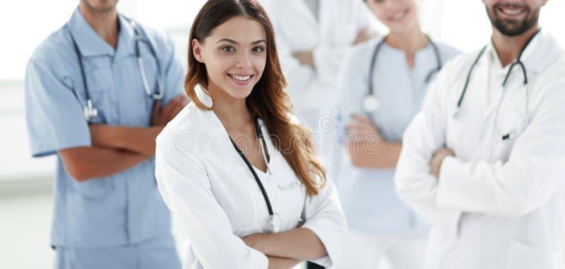 Atrakcyjna kobiety lekarka z medycznym stetoskopem przed medyczną grupą obrazy royalty free