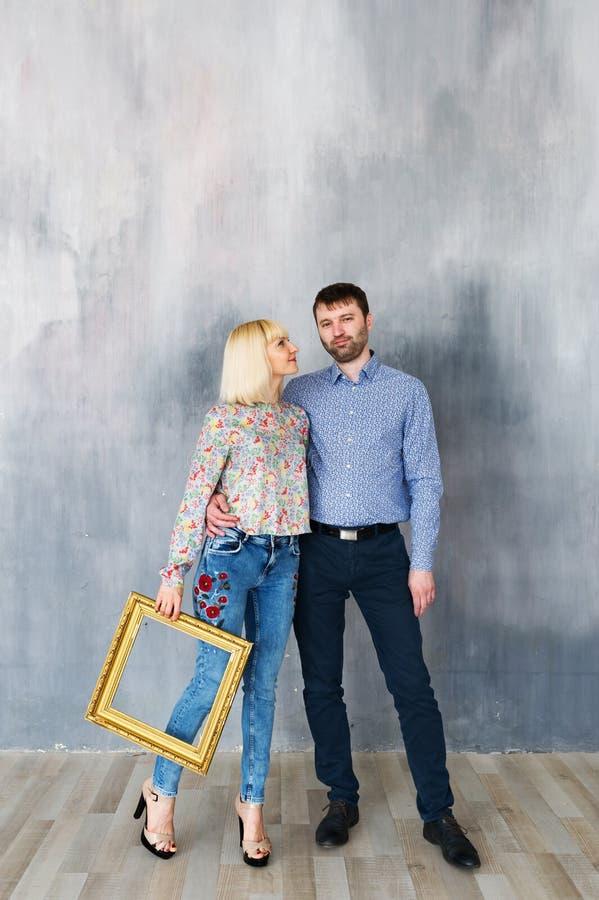 Atrakcyjna kochająca para jest trwanie blisko tekstury ściany, spojrzenia przy kamerą i ono uśmiecha się, zdjęcia royalty free
