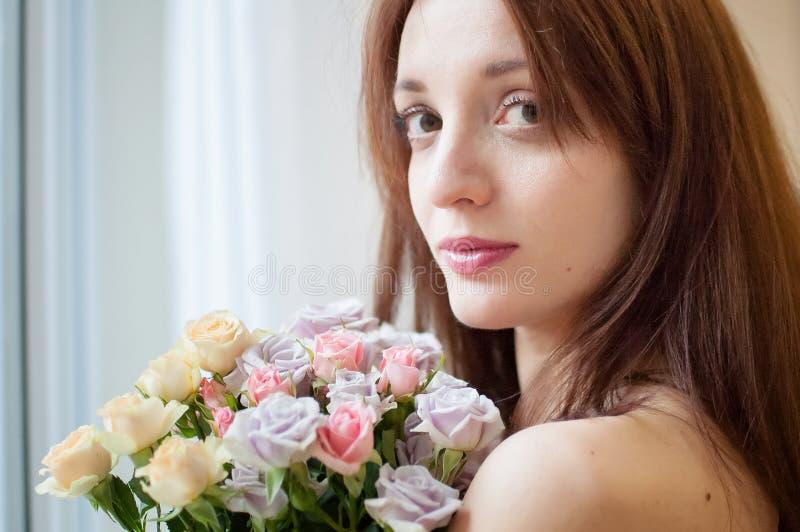 Atrakcyjna młoda brunetki kobieta patrzeje kamerę trzyma bukiet kwiaty zdjęcie royalty free