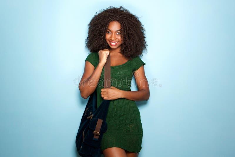 Atrakcyjna młoda amerykanin afrykańskiego pochodzenia kobieta w pięknej sukni i torebce na błękitnym tle zdjęcia stock