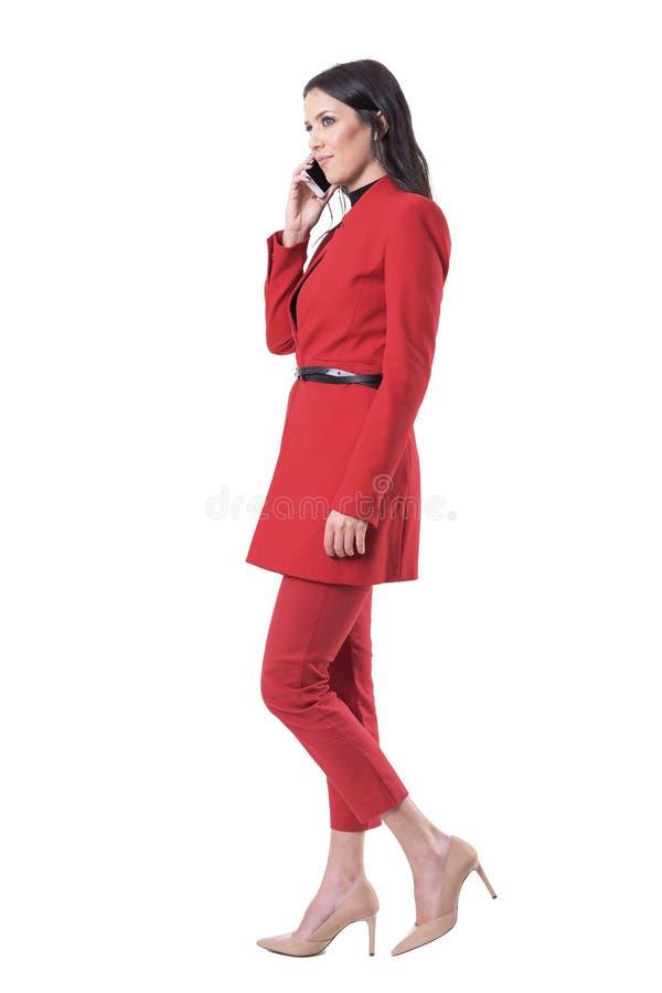 Atrakcyjna młoda biznesowa kobieta opowiada na telefonu odprowadzeniu i przyglądająca w górę w czerwonym kostiumu zdjęcie royalty free