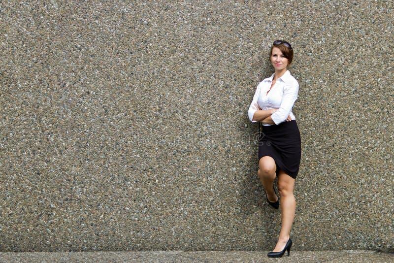 Atrakcyjna młoda biznesowa kobieta pozuje przeciw popielatej ścianie - kopia obrazy royalty free