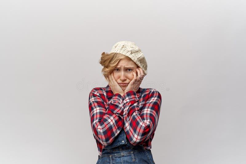 Atrakcyjna młoda blond studencka dziewczyna w niemodnym odziewa w retro stylu jak hillbilly w zamieszaniu chwyta jej twarz w ręka obrazy royalty free