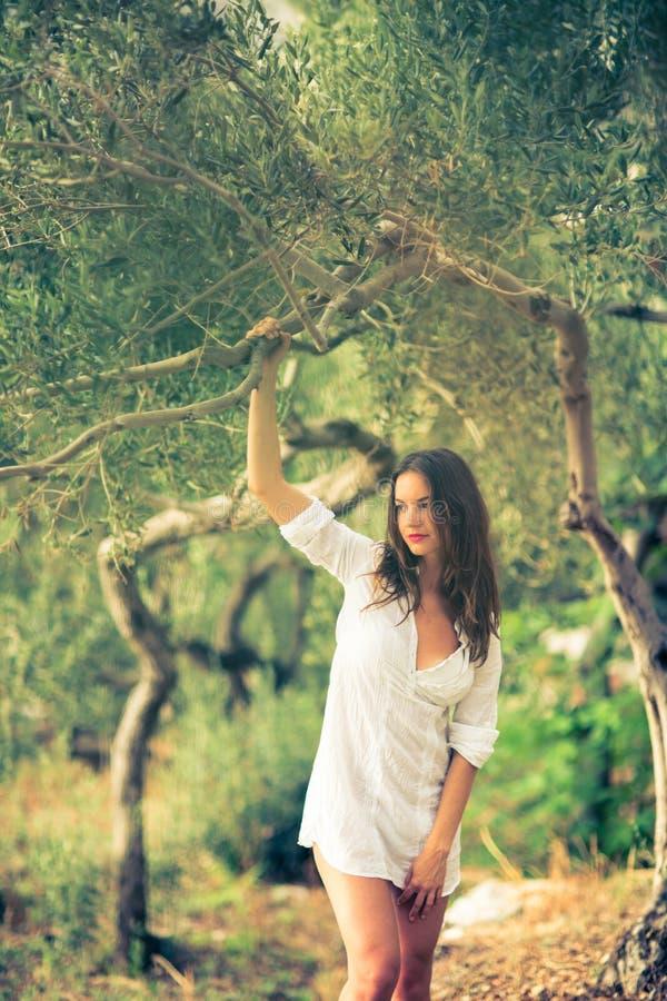 Atrakcyjna, młoda brunetka na plaży wśród drzew oliwnych, zdjęcie stock