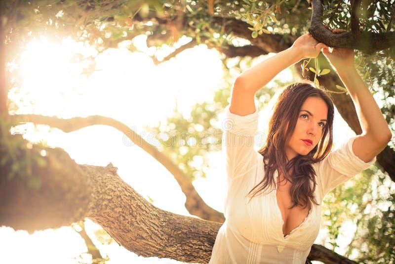 Atrakcyjna, młoda brunetka na plaży wśród drzew oliwnych, zdjęcia royalty free