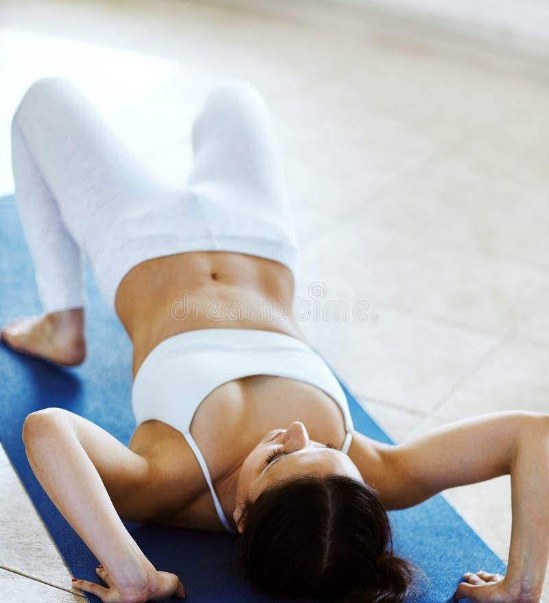Atrakcyjna młoda brunetki kobieta robi joga lub pilates ćwiczymy dla plecy i ręki rozciągliwości w gym z biel ścianą obrazy royalty free