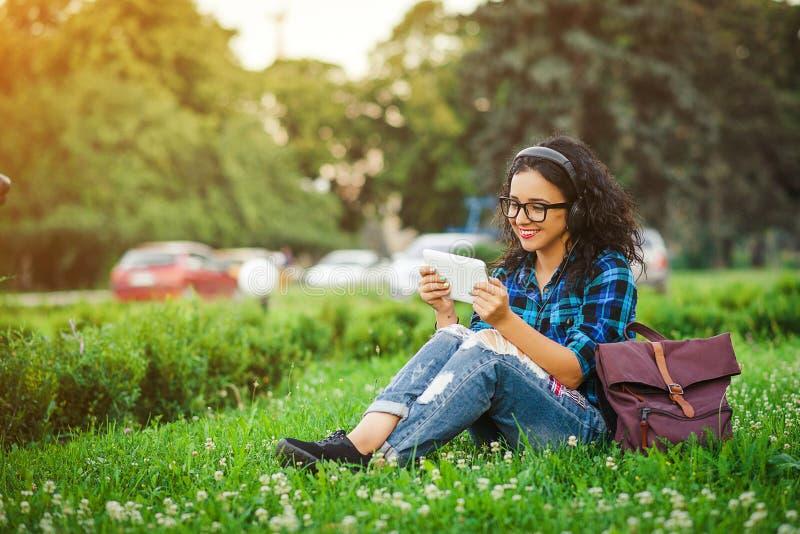 Atrakcyjna młoda dziewczyna używa pastylkę plenerową zdjęcie royalty free