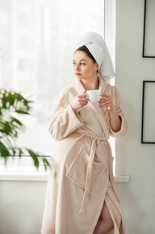 Atrakcyjna młoda dziewczyna w bathrobe z ręcznikiem na jej głowie i trzyma filiżankę, siedzi na nadokiennym parapecie w łazience fotografia stock