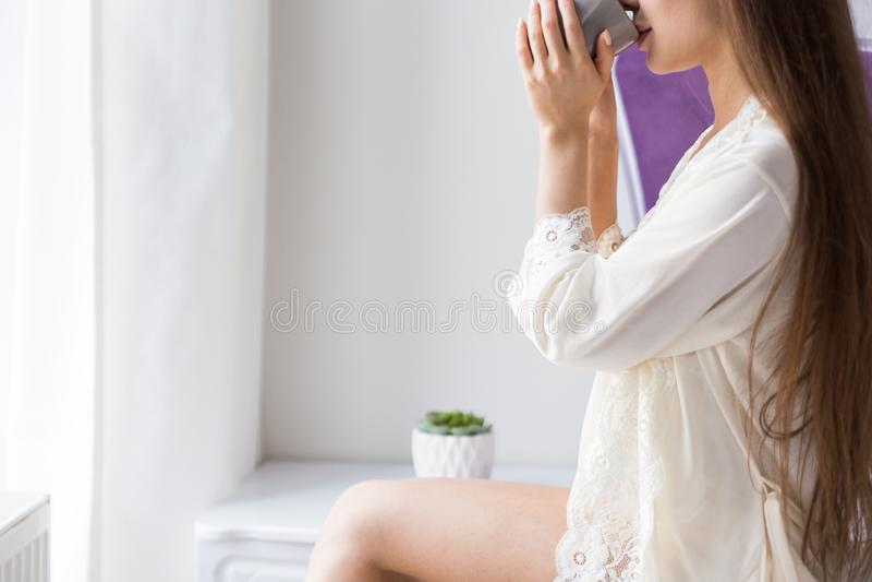 Atrakcyjna młoda dziewczyna w nightwear siedzi na krawędzi łóżka okno i pije kawę od kubka zdjęcia royalty free