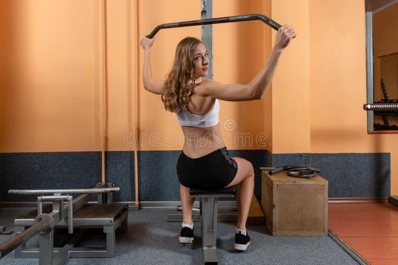 Atrakcyjna młoda dziewczyna w sport odzieży opracowywa z sprawności fizycznej wyposażeniem w fachowym gym TARGET1051_1_ w gym obrazy stock