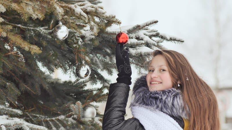 Atrakcyjna młoda dziewczyna z długie włosy w zima kostiumu pozuje przeciw śnieżnemu drzewu Dziewczyna zawiązuje Bożenarodzeniowe  zdjęcie royalty free