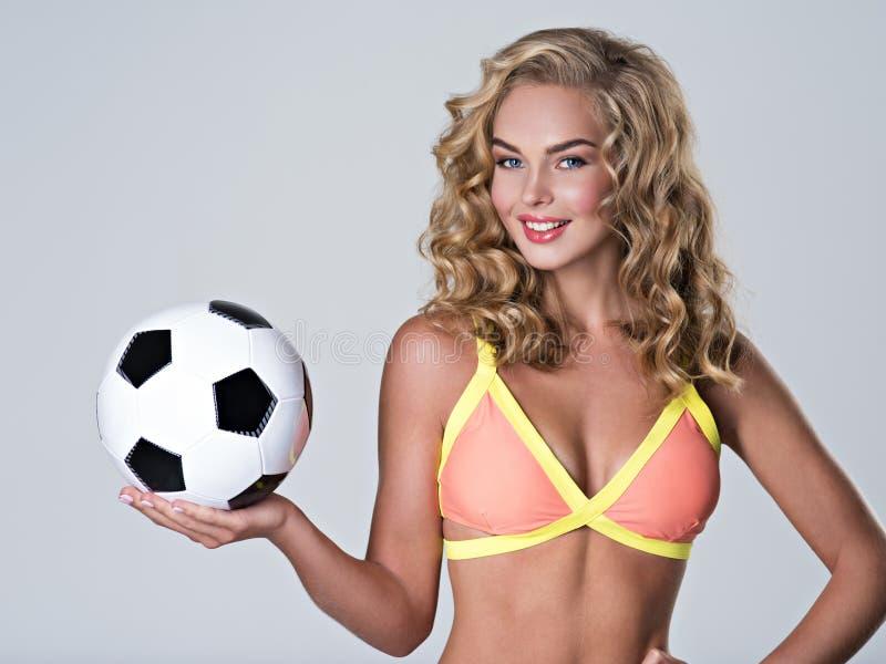 Atrakcyjna młoda dziewczyna z klasyczną piłki nożnej piłką na palmie fotografia stock