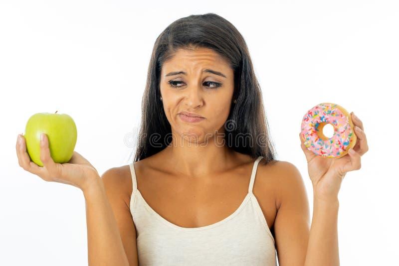 Atrakcyjna młoda kobieta decyduje między jabłkiem i pączkiem na diecie fotografia royalty free