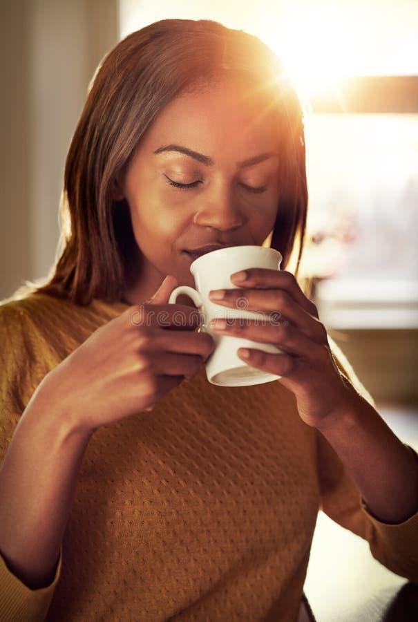Atrakcyjna młoda kobieta delektuje się filiżankę kawy obrazy royalty free