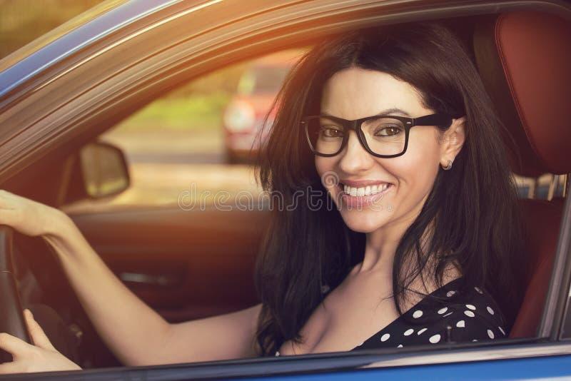 Atrakcyjna młoda kobieta jedzie jej samochód obrazy stock