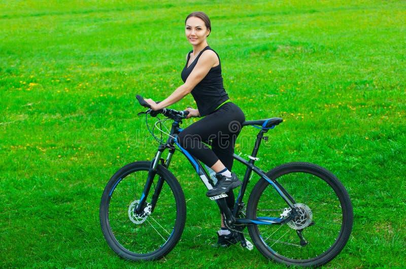 Atrakcyjna młoda kobieta jedzie rower górskiego w parku obraz royalty free