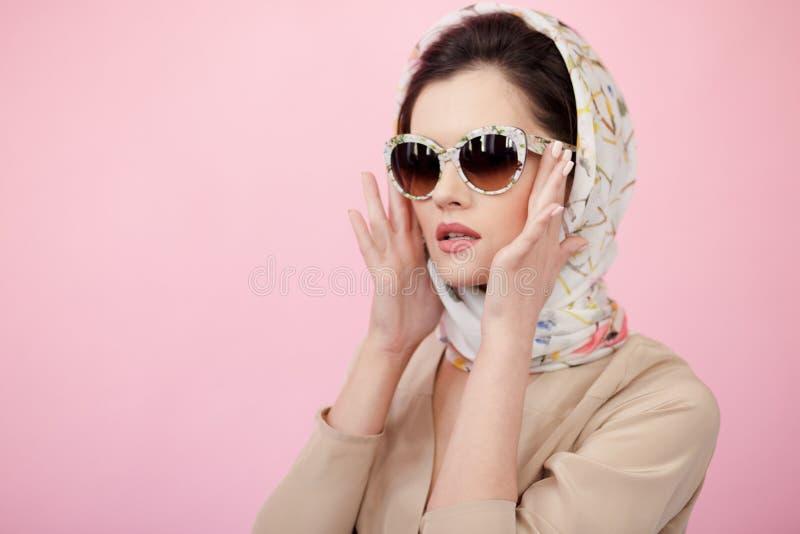 Atrakcyjna młoda kobieta jest ubranym w jedwabniczym szaliku, dotyki na różowym tle jego okulary przeciwsłoneczni z jego rękami,  fotografia royalty free