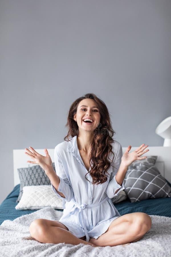 Atrakcyjna młoda kobieta ono uśmiecha się na łóżku w domu obraz royalty free