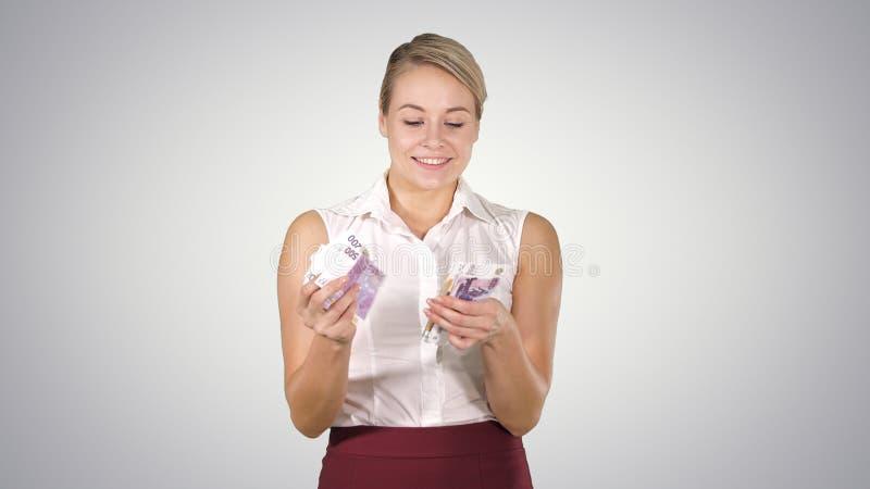 Atrakcyjna młoda kobieta ono uśmiecha się na gradientowym tle liczy euro obrazy royalty free