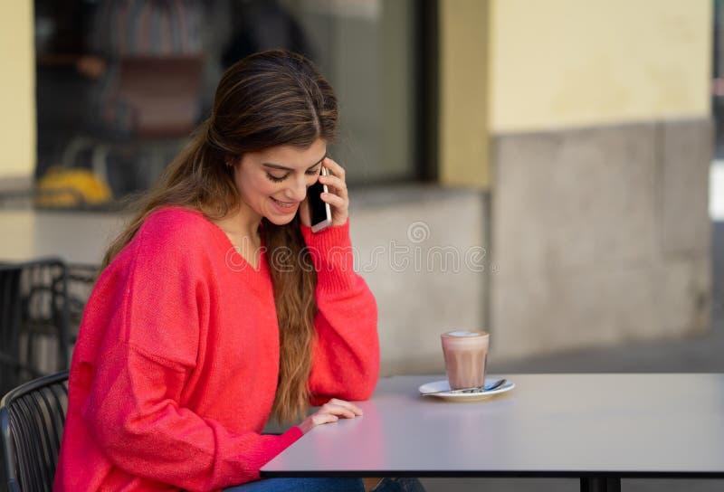 Atrakcyjna młoda kobieta opowiada na jej mądrze telefonie komórkowym w sklepu z kawą tarasie zdjęcie stock