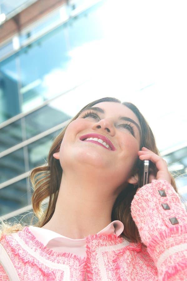 Atrakcyjna młoda kobieta opowiada na telefonie komórkowym w mieście fotografia royalty free