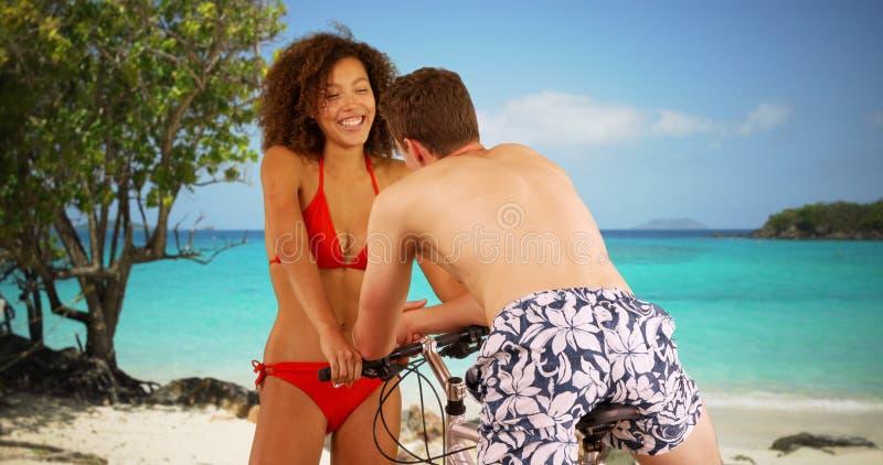 Atrakcyjna młoda kobieta opowiada z pojedynczym mężczyzna na rowerze w bikini zdjęcia stock