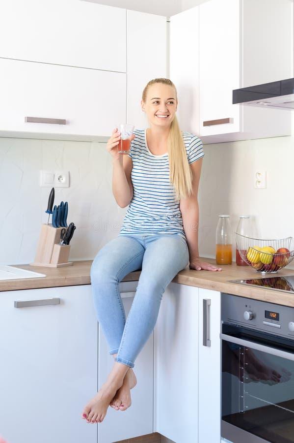 Atrakcyjna młoda kobieta pije domowej roboty owocowego soku obsiadanie na kuchennym kontuarze Młoda gospodyni domowa relaksuje w  zdjęcie royalty free