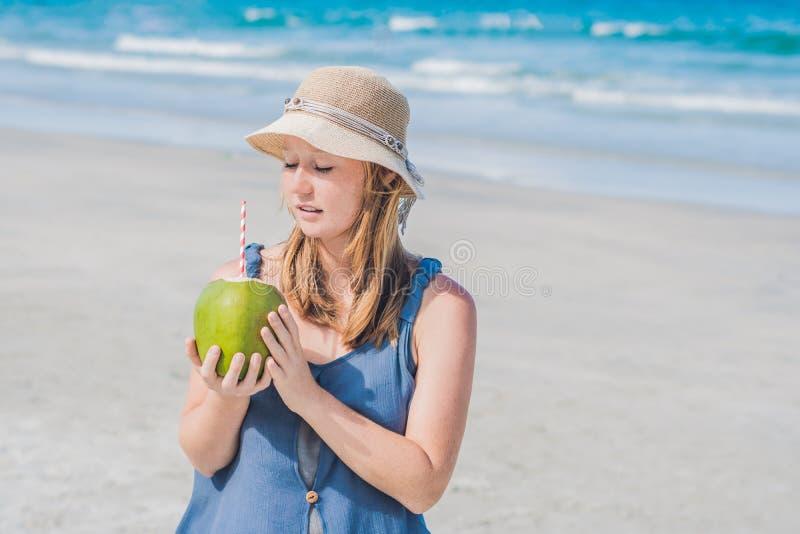 Atrakcyjna młoda kobieta pije koks wodę na plaży obrazy stock