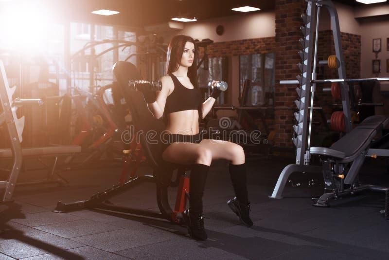 Atrakcyjna młoda kobieta pracująca z dumbbells w gym out Sprawności fizycznej dziewczyna wykonuje ćwiczenie fotografia royalty free