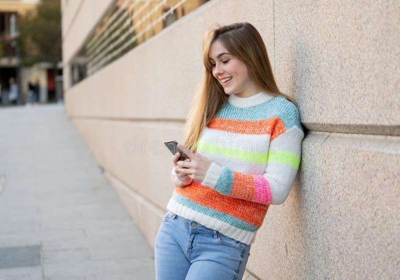Atrakcyjna młoda kobieta sprawdza ogólnospołecznych medialnych mobilnych apps na zewnątrz miasta na mądrze telefonie zdjęcie royalty free